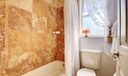 Guest tub and marble tiled wall