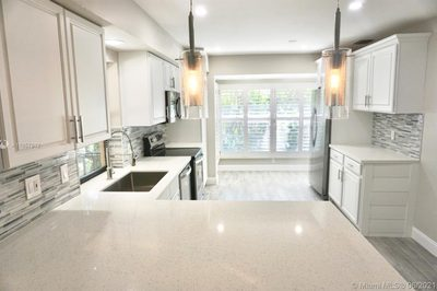 Beautifully updated kitchen with all NEW stainless steel appliances, sparkling quartz countertop, and wood tile flooring.