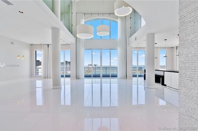 Enter into your 2 story top floor Penthouse with 30+ ft ceilings and a giant living/dining/kitchen area with stunning bay/ocean/city views.