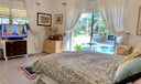 Master overlooks tropical screened pool patio and garden view