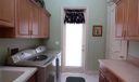 Large first floor laundry room with sink and ample storage