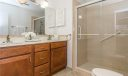 Gorgeous master bath with beautiful updated custom vanity with his and her sinks, tile flooring, walk in shower, new lighting fixtures and commode.