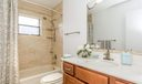 Renovated Guest Bath with custom maple vanity with beautiful fixtures and hardware. Look at the beautiful touches in the shower with decorative tile and new shower head. A sunlit bathroom you won't want to leave!