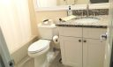 Your spare bathroom, with tile on the diagonal, offers Thomasville soft-close cabinetry.