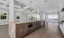 """Maple cabinetry with Cambria """"Britanica"""" waterfall countertop and island.  Jenn-Air Microwave and Dishwasher.  Breakfeast/Dining off kitchen with expansive river views."""