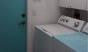 laundry is located inside the home, close to kitchen. Blue door exits to 2-car garage.